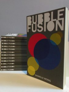 Bubble Fusion title in white in bubble text on a gray background; red, blue, and yellow bubbles on the cover.  Spine of copies of book.